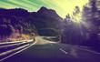 Quadro Concepto de viajes por carretera.Carretera de montaña con curvas y puesta de sol.Seguridad y precaución conduciendo.