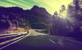 Concepto de viajes por carretera.Carretera de montaña con curvas y puesta de sol.Seguridad y precaución conduciendo. - 191665118