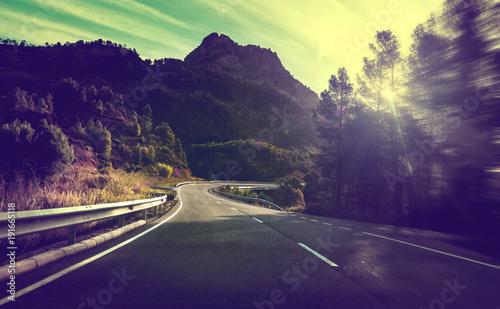 Staande foto Weg in bos Concepto de viajes por carretera.Carretera de montaña con curvas y puesta de sol.Seguridad y precaución conduciendo.