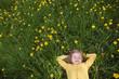 Happy little girl dreams on a green glade of dandelions