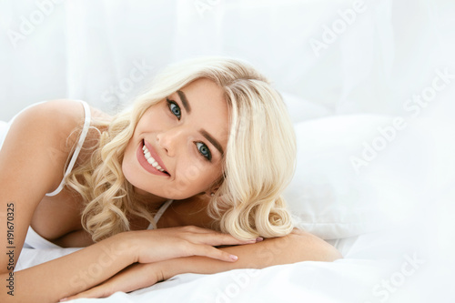 Happy Woman With Beautiful Face Smiling, Lying On Bed.