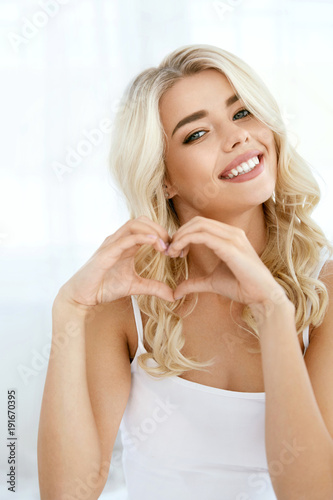 Love. Beautiful Smiling Woman Showing Heart With Hands