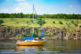 Beautiful scenery of sailing yacht with rocky coast on background.