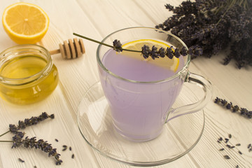 Lavender tea with honey and lemon on the white wooden background