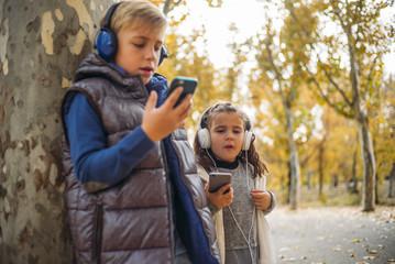 Children listen to music in autumn landscape..