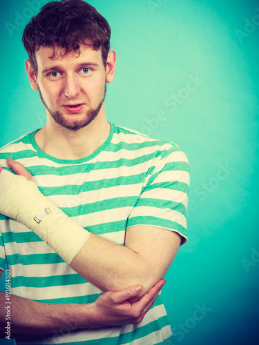 Man with painful bandaged hand.