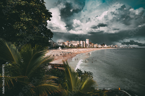Fotobehang Rio de Janeiro Wide-angle shooting of stunning cityscape during the storm in Rio de Janeiro: coastline with Leblon and Ipanema beaches, swimming and tanning people, dramatic sky with heavy rain in distance, palms