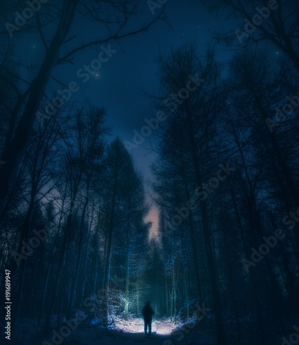 Fotobehang Nachtblauw Surreal night forest landscape with alone strange man with flashlight.