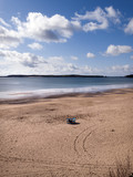 A solitary windbreak set up in early spring sunshine on South Beach, Tenby, Pembrokeshire, UK - 191698119