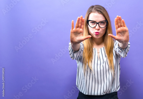 Young woman making a rejection pose on a solid background