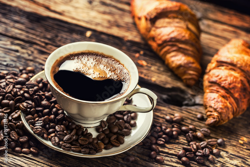 Coffee. Cup of coffee croissants and coffee beans. Vintage cup and old oak table