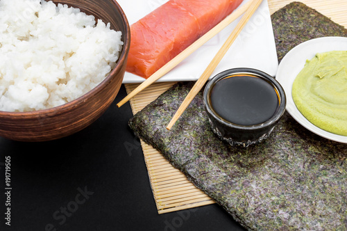 Keuken foto achterwand Sushi bar Ingredients for sushi with bamboo mat on black background.
