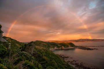 Rainbow and sunset along ocean coastline
