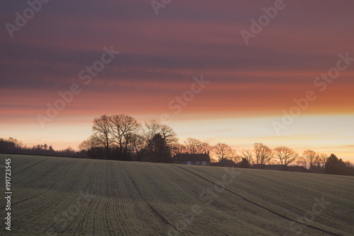 Foto Murales Beautiful vibrant Winter sunrise over farmhouse in English countryside landscape