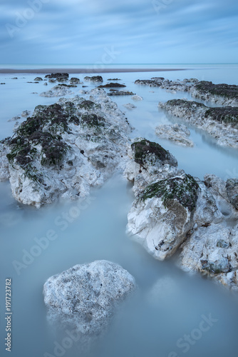 Foto op Canvas Blauwe hemel Stunning long exposure landscape image of low tide beach with rocks at sunrise