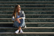 Beautiful young caucasian woman with eyes closed sitting on steps