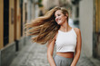 Happy young woman with moving hair in urban background. - 191724179