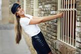 Young blonde woman wearing cap smiling near a brick wall.