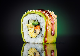 Sushi roll over black background. Sushi roll with eel, tofu, vegetables and avocado closeup. Japanese food