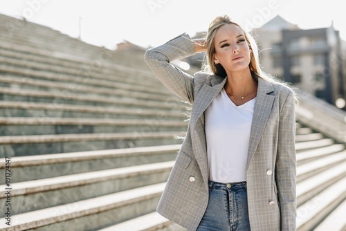 obraz lub plakat Beautiful young blonde woman in urban background.