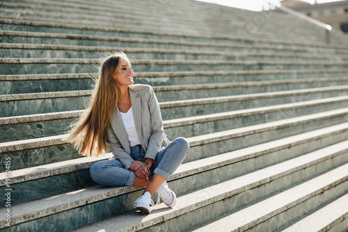 Foto Murales Beautiful young blonde woman smiling on urban steps.