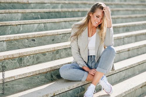 fototapeta na ścianę Beautiful young blonde woman smiling on urban steps.