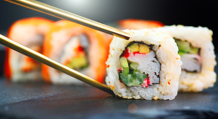 Sushi rolls. Japanese food in restaurant. Sushi roll set california with salmon, vegetables, flying fish roe and caviar closeup