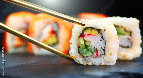 Keuken foto achterwand Sushi bar Sushi rolls. Japanese food in restaurant. Sushi roll set california with salmon, vegetables, flying fish roe and caviar closeup
