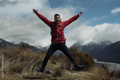 Foto op Canvas Blauwe jeans Hombre joven con chaquetón rojo saltando frente a montañas con picos nevados en Nueva Zelanda