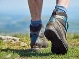 A close up of a female hikers muddy walking boots on a bright sunny day - 191739716