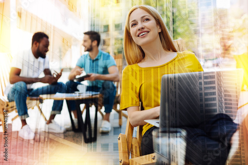 Noticing friends. Pretty smiling young woman sitting in a cafe with a laptop on her knees and feeling happy while noticing her best friend in a crowd
