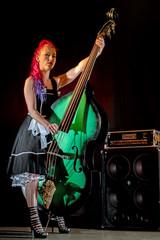 Rock'n'Roll Sängerin mit roten Haaren, Kontrabass und Lautsprecher auf einer Bühne