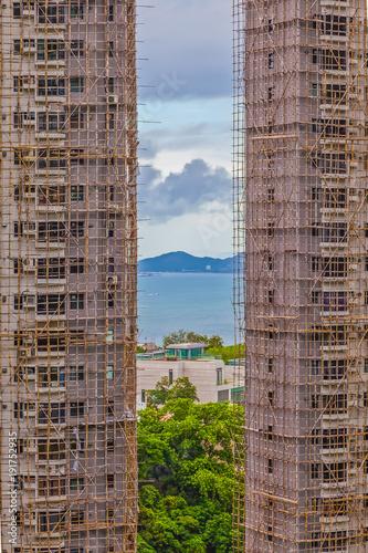 Aufnahme von im Bau befindlichen Hochhäusern mit typischem traditionellem Baugerüst aus Bambusstangen mit der Bucht von Hongkong im Hintergrunf aufgenommen im Jahr 2013