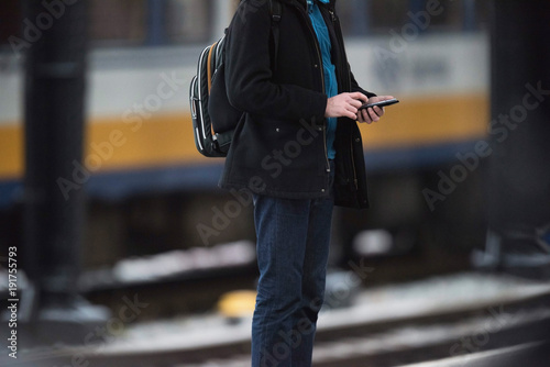 Traveler with backpack checking smartphone while standing on platform waiting for train.