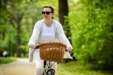 Urban biking - woman riding bike in city park - 191756109