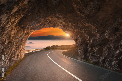 Fotobehang Chocoladebruin Old road tunnel in mountains at beautiful sunrise