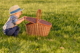Toddler child outdoors. One year old baby boy wearing straw hat looking in picnic basket - 191771775