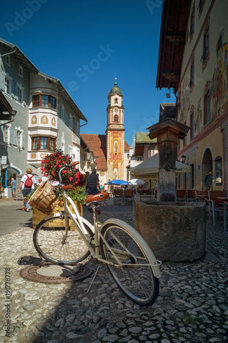 Foto op Canvas Fiets White vintage bicycle with basket on Obermarkt stone paved street in old German city of Mittenwald