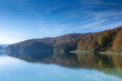 Reflection of a peninsula on a lake. Taken in Plitvice Lakes National Park. The sky is mostly clear with few clouds and the trees are turning colors.