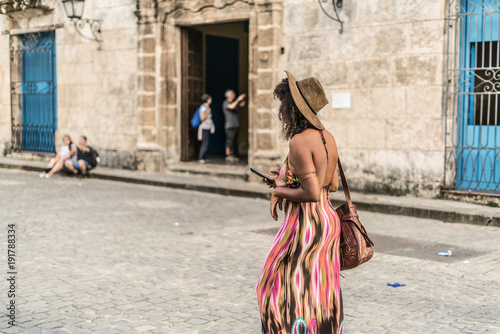 fototapeta na ścianę young beautiful woman using her telephone for taking images or video, maybe taking a self in the center of cuba, Havana.