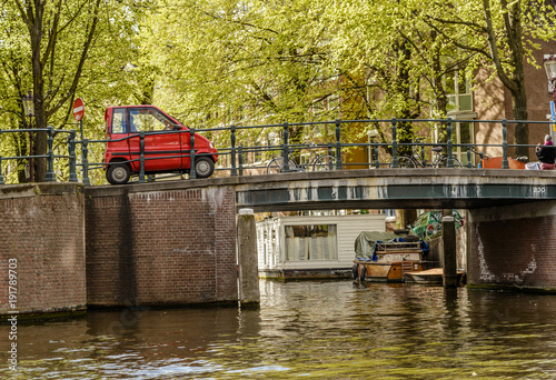 Papiers peints Amsterdam Mini Car crossing a Bridge in Amsterdam canal, Netherlands