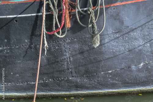 Aluminium Schip Detail of black ship hull with ropes in sunny day. Vintage dark metal background.