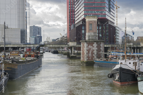 Tuinposter Rotterdam Details of old harbor of Rotterdam in cloudy day in November at low tide illustrating modern urban landscape with water, ships and tall buildings, Rotterdam, Netherlands.