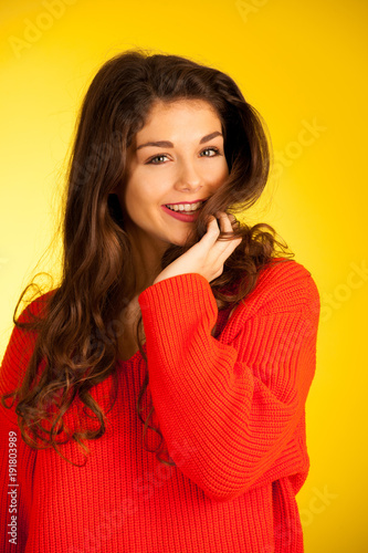 Beautiful young caucasian woman in orange sweater over yellow background - confident teenager