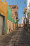 Narrow, hilly stone paved street, with colorful houses and other architectural details, in Guanajuato, Mexico - 191813109