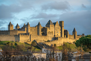 Walls and towers of Carcassonne in golden light of setting sun, Aude, France