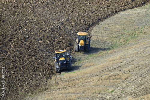 Papiers peints Toscane Two caterpillar tractors are working in the field
