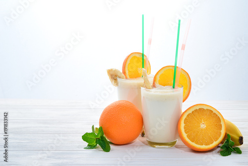 Smoothies with bananas and oranges, a sprig of mint on a white background. Space for text or design.