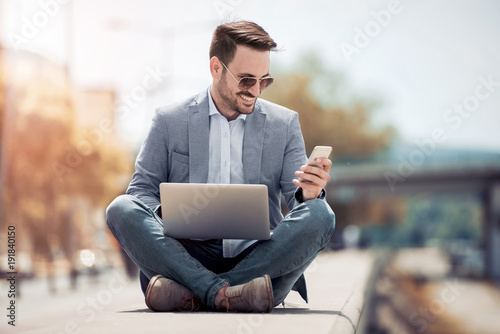 Young attractive man sitting outside on concrete while using cell phone.