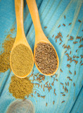 Ground cumin in a spoon and whole cumin on the wooden background. - 191841945